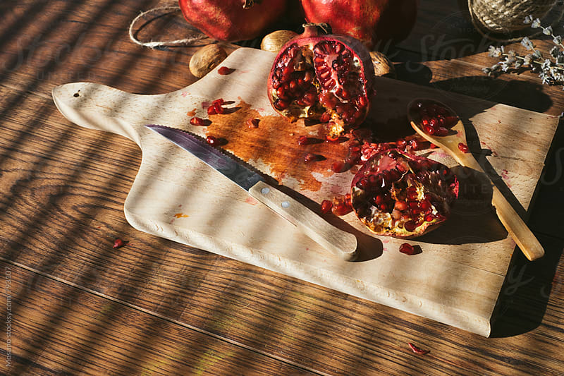 Squashed Pomegranate on a Wooden Table by Mosuno for Stocksy United