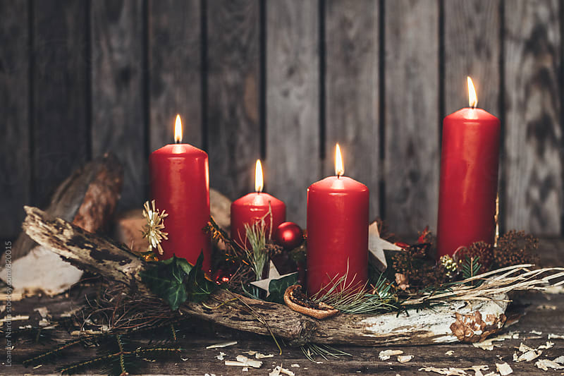 rural decorated floral advent arrangement with four red burning candles by Leander Nardin for Stocksy United