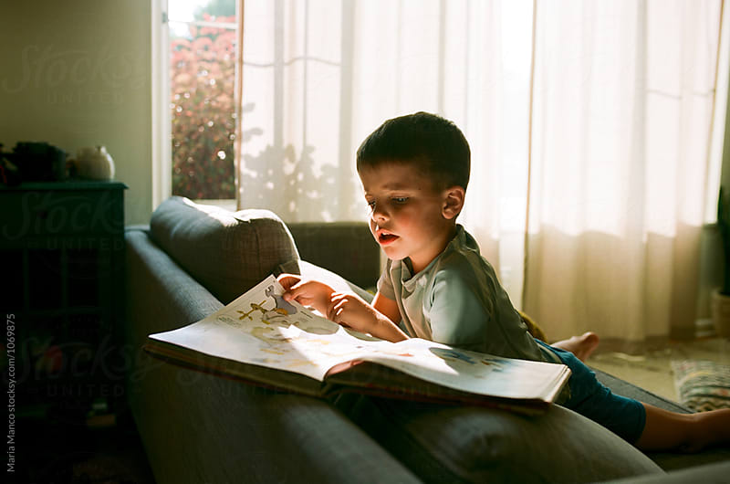 boy doing homework on couch by Maria Manco for Stocksy United