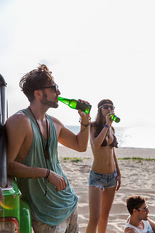 Friends relaxing and drinking beer at the beach  by Jovo Jovanovic for Stocksy United
