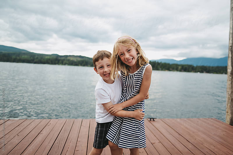 Brother and sister goofing around at the lake by Rob and Julia Campbell for Stocksy United