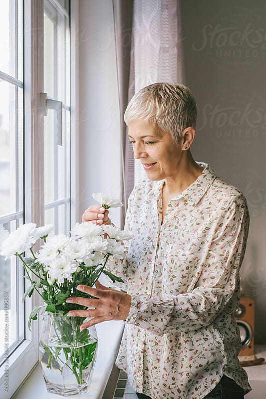Senior Woman Arranging the Flowers in a Vase by Aleksandra Jankovic for Stocksy United