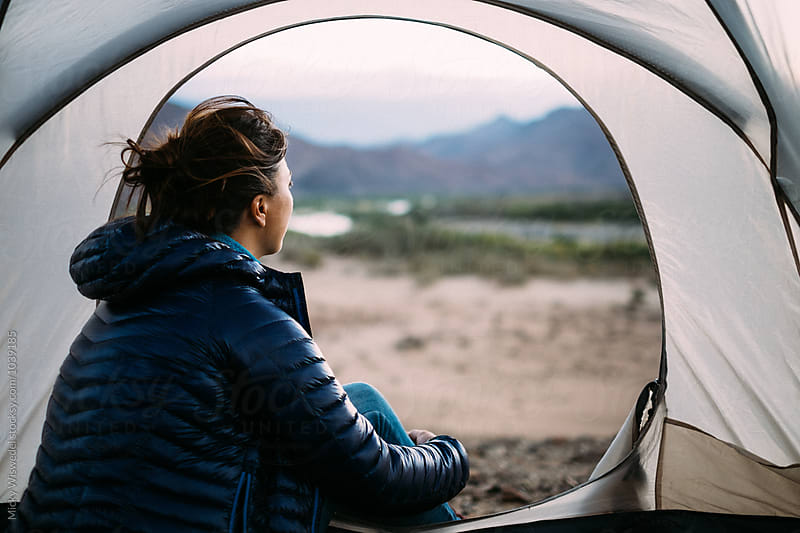 Woman sitting in her camp tent taking in the view of the outdoors at dawn by Micky Wiswedel for Stocksy United