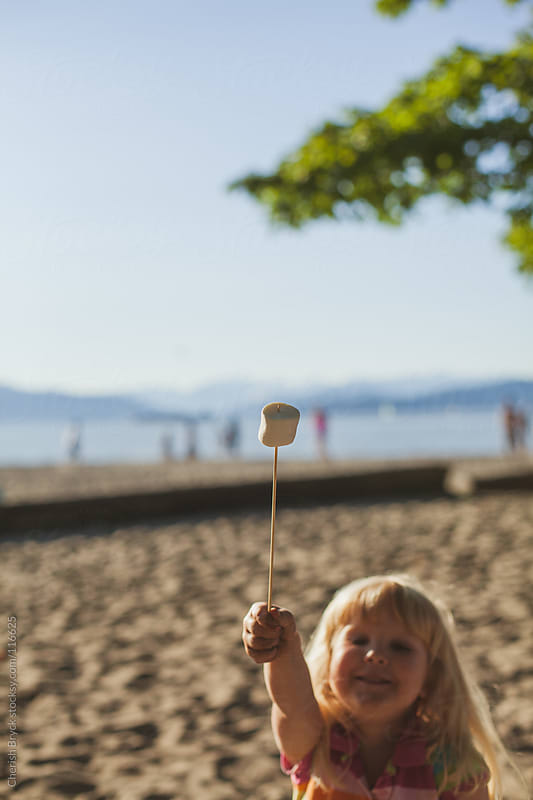 Little girl holds up roasted marshmallow. by Cherish Bryck for Stocksy United