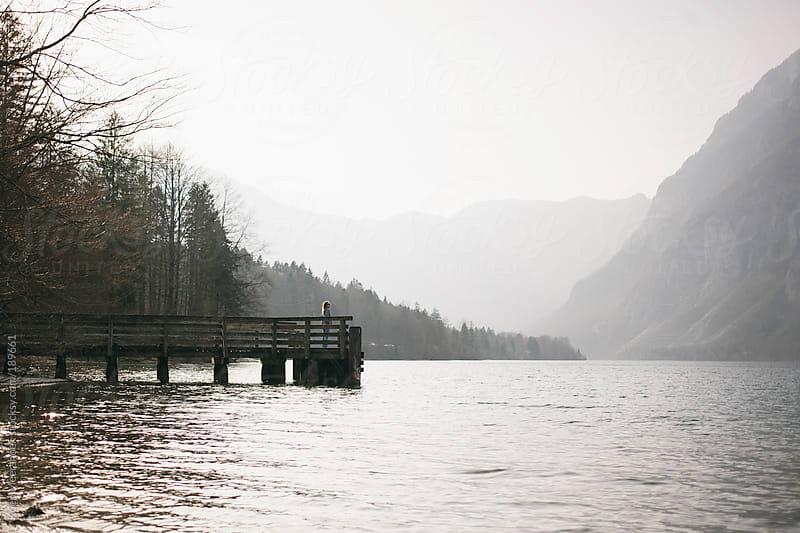 Girl standing on a platform at a big lake in Slovenia. by Koen Meershoek for Stocksy United