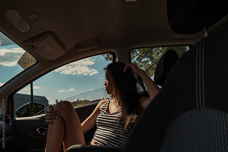Young asian woman looking out passenger side window by Eddie Pearson for Stocksy United