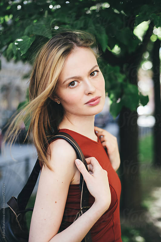 Beautiful woman with a backpack looking at camera by Lyuba Burakova for Stocksy United