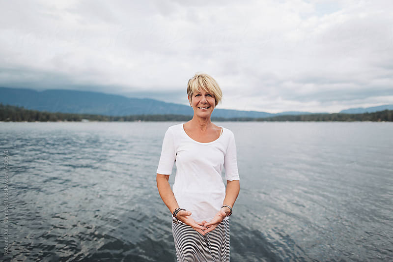 Portrait of mature woman near water smiling by Rob and Julia Campbell for Stocksy United