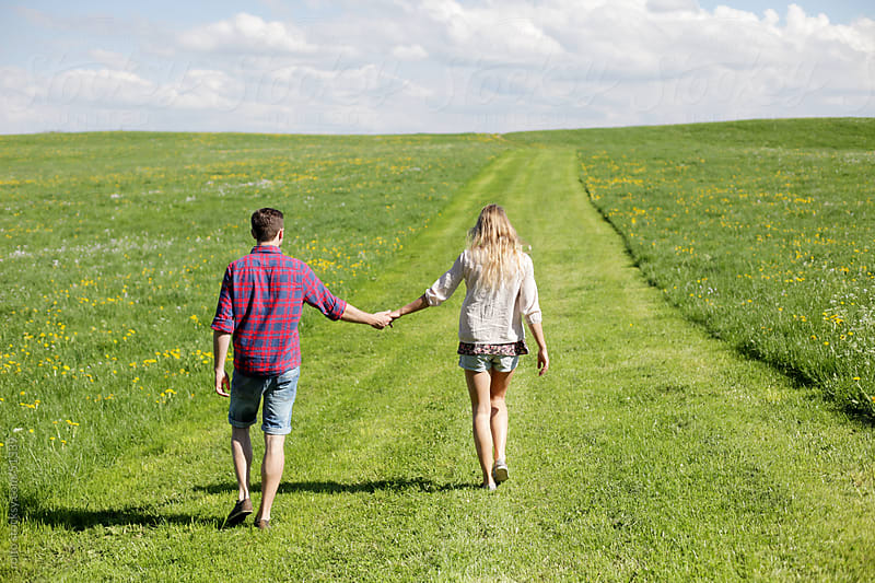 young couple walking way of a field  by rolfo for Stocksy United