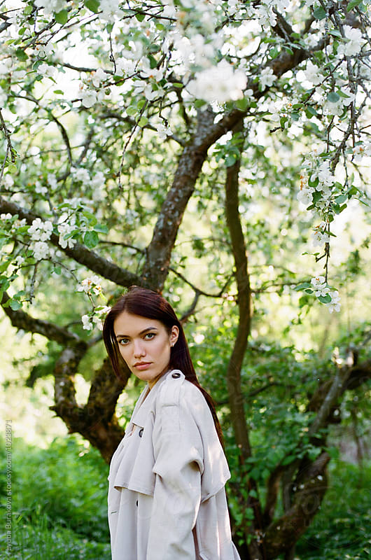 Young woman at apple tree in blossom by Lyuba Burakova for Stocksy United