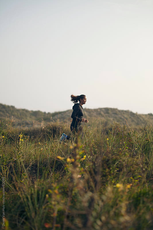 Young woman running through the dunes by Denni Van Huis for Stocksy United