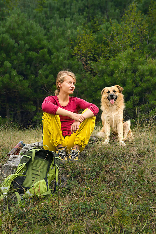 Hiker woman with dog relaxing together in the nature by RG&B Images for Stocksy United