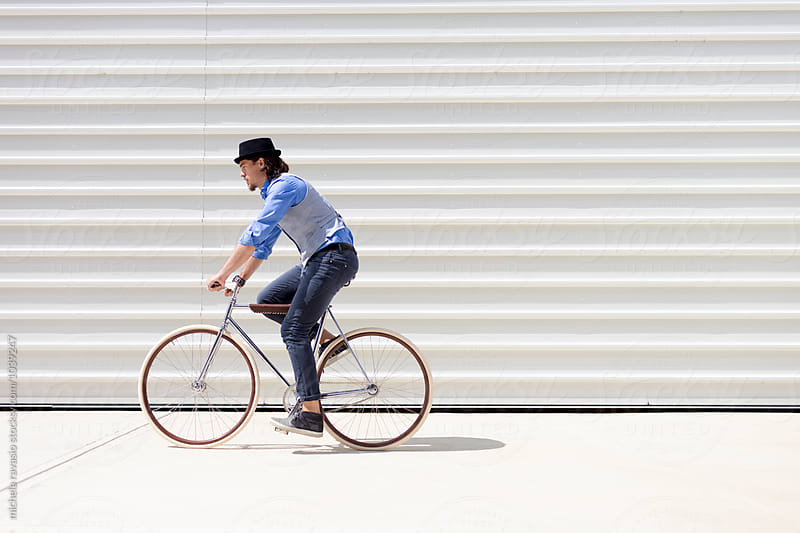 Fashionable man riding his stylish bicycle by michela ravasio for Stocksy United