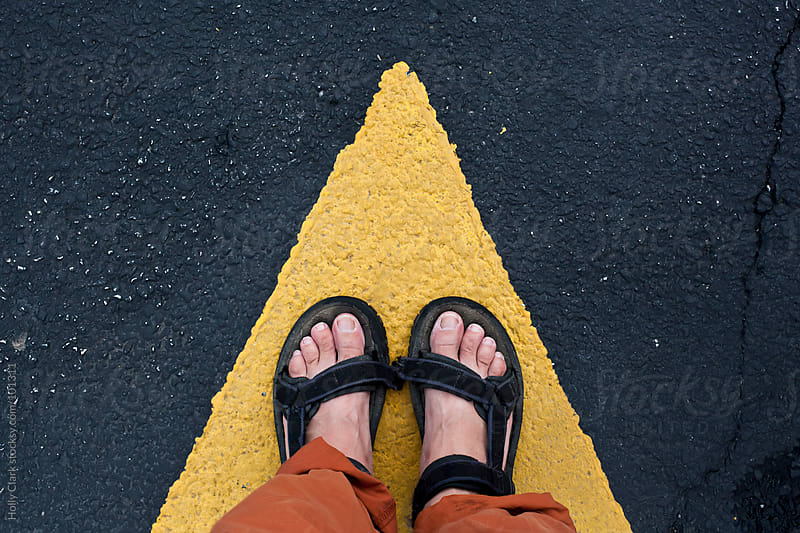 A woman's feet standing on the tip of a yellow arrow painted on  by Holly Clark for Stocksy United