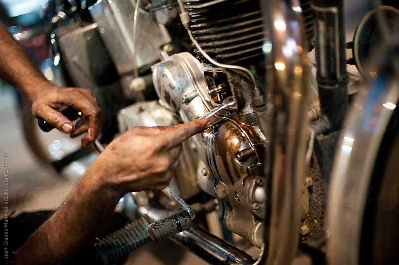 Mechanic working on the engine of an old bike in his workshop by Jean-Claude Manfredi for Stocksy United