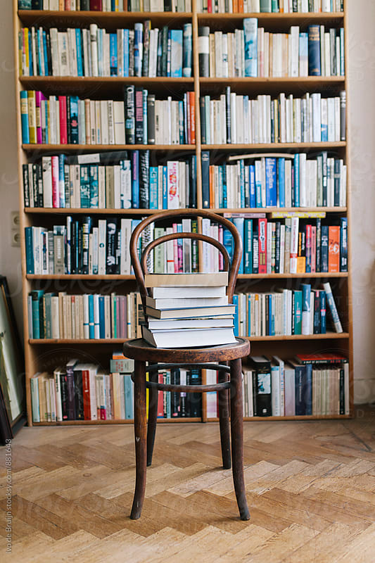 A classic chair with a pile of books in front of a bookcase by Ivo de Bruijn for Stocksy United