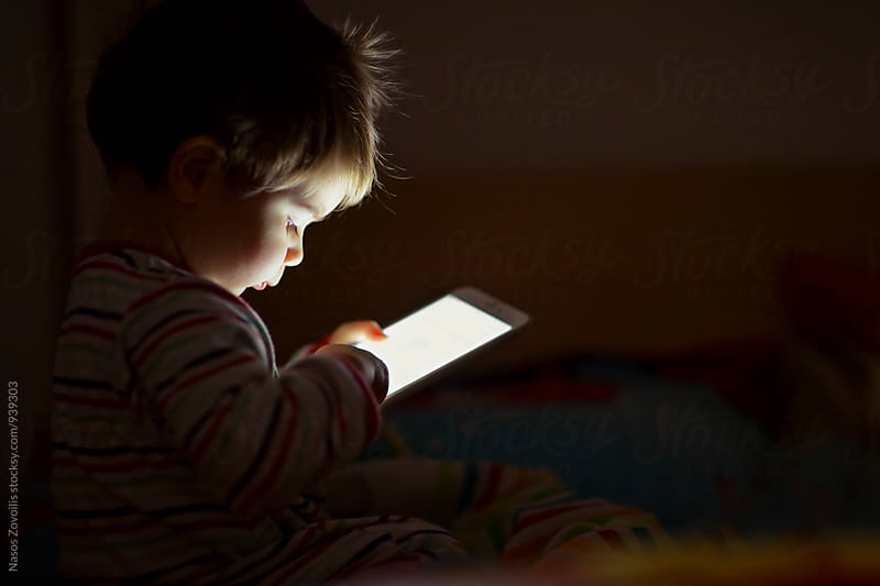 1 year old boy looking a digital tablet in the dark by Nasos Zovoilis for Stocksy United