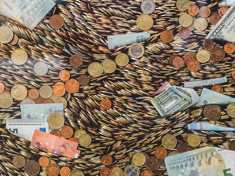 a huge pile of coins and banknotes by Juri Pozzi for Stocksy United
