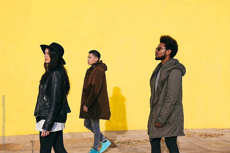 Side view of friends walking in front of a yellow wall on winter. by BONNINSTUDIO for Stocksy United