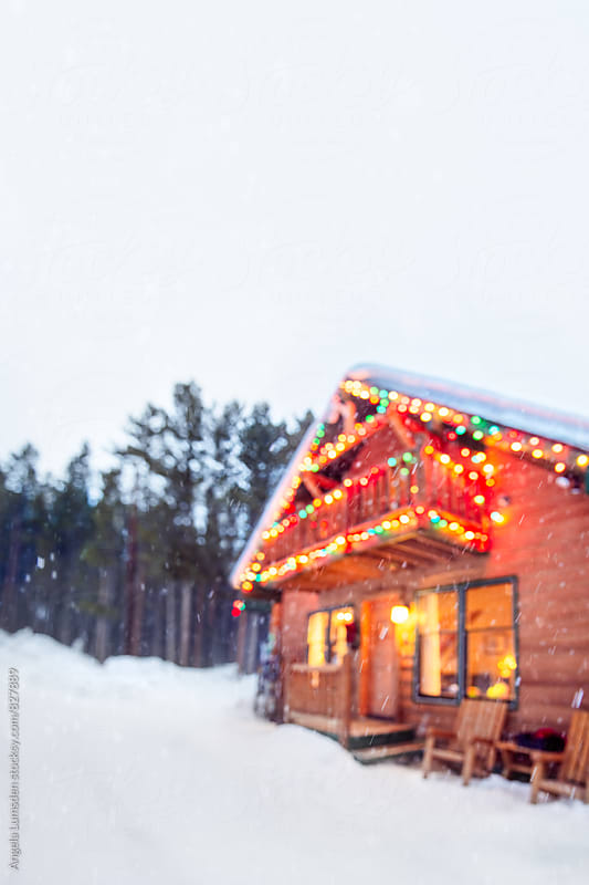 Festive ski cabin decorated with holiday lights in a snowy setting by Angela Lumsden for Stocksy United