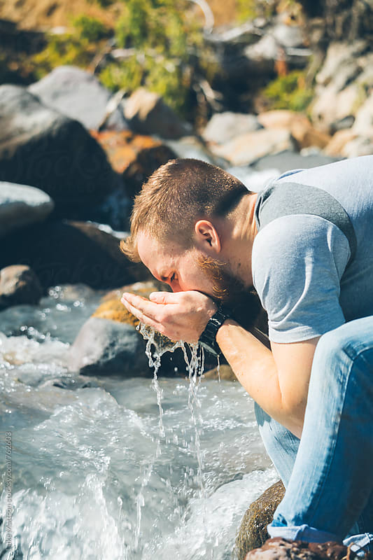 Blond Bearded Man Drinking Water From River On Hike by Luke Mattson for Stocksy United
