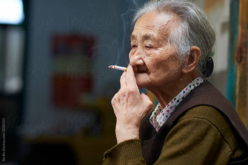 senior woman smoking by cuiyan Liu for Stocksy United
