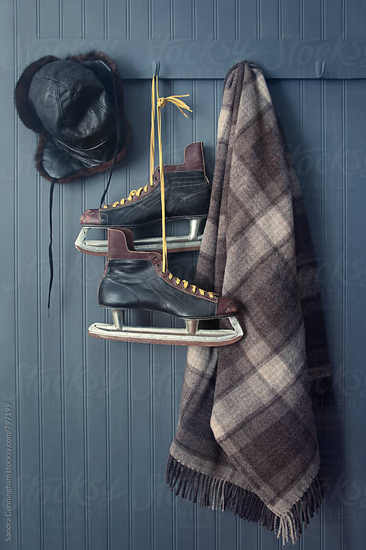 Old men's skates with hat and blanket on hooks by Sandra Cunningham for Stocksy United