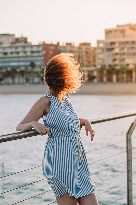 Young woman on a bridge on a windy day by Vera Lair for Stocksy United