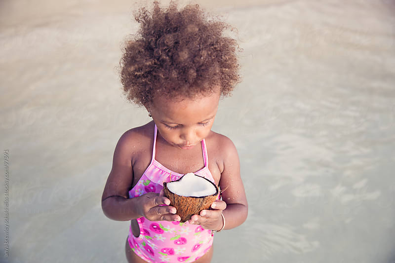 Portrait of young girl with curly brown hair holding a cracked open coconut by anya brewley schultheiss for Stocksy United