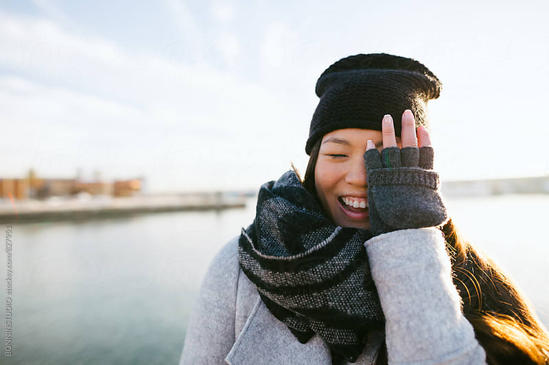 Portrait of an asian woman laughing outside on wintertime. by BONNINSTUDIO for Stocksy United