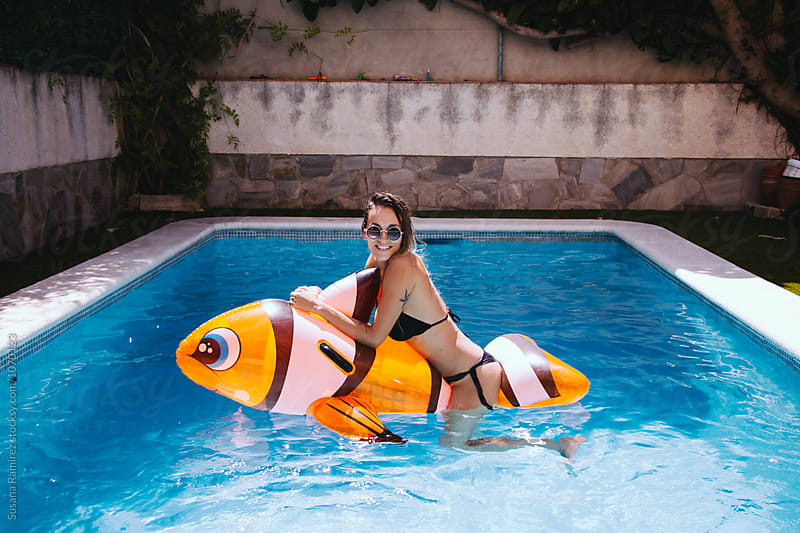 Funny young woman on top of a mattress fish in the pool by Susana Ramírez for Stocksy United