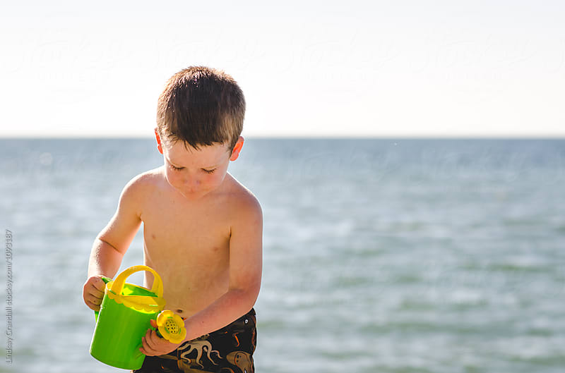 Little boy using watering can by the lake by Lindsay Crandall for Stocksy United