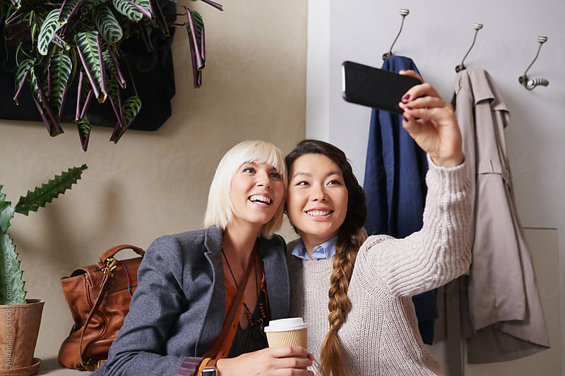 Stylish young women friends taking selfie on smart phone in cafe by Aila Images for Stocksy United