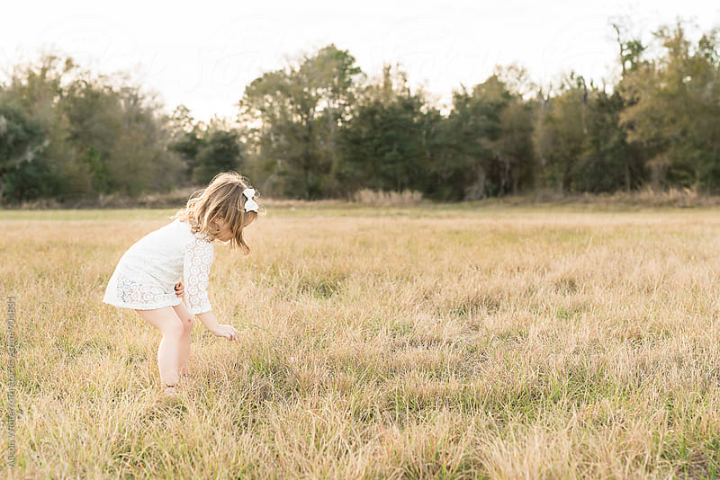 Little Girl Crouching To Pick Flowers by Alison Winterroth for Stocksy United