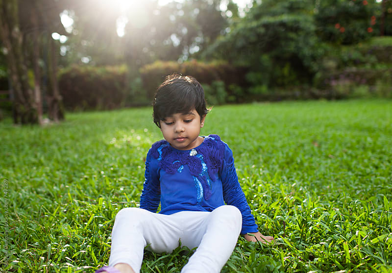 Little girl sitting in the lawn in a thoughtful mood by Saptak Ganguly for Stocksy United
