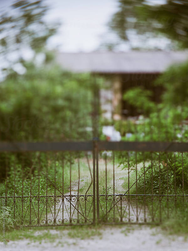 Lensbaby catch of a gate in front of abandoned ancient italian farm by Laura Stolfi for Stocksy United