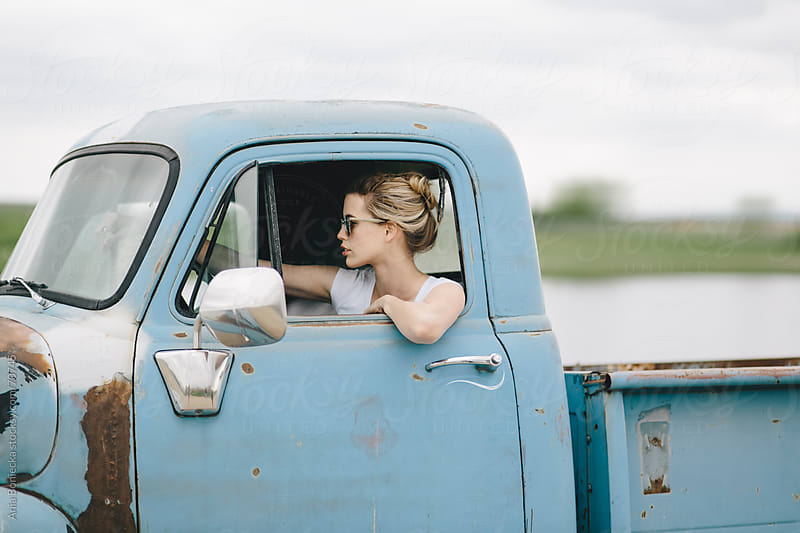 Blond girl driving an old pickup truck by Ania Boniecka for Stocksy United