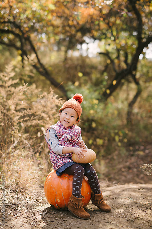 Cut baby girl with pumpkins on autumn by Maa Hoo for Stocksy United