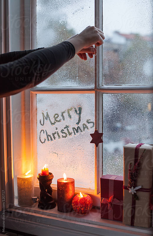 Lighting christmas candles next to the window.  by Mosuno for Stocksy United