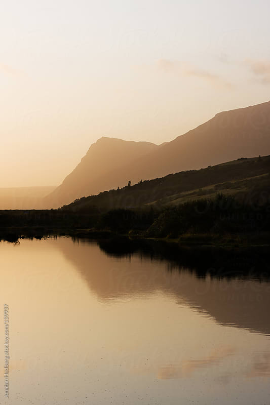 Sunset over a small lake by Jonatan Hedberg for Stocksy United