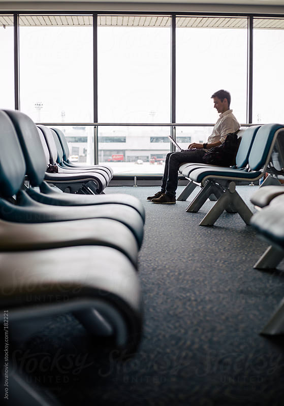 Man working on airport while waiting for his flight by Jovo Jovanovic for Stocksy United