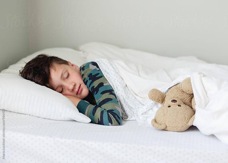 Boy sleeping with old teddy bear by Marta Locklear for Stocksy United