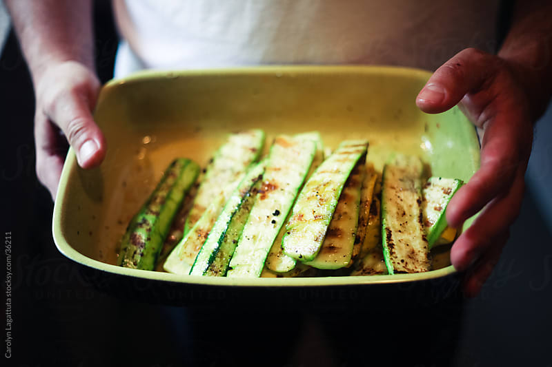Man holding a green dish of grilled zucchini by Carolyn Lagattuta for Stocksy United