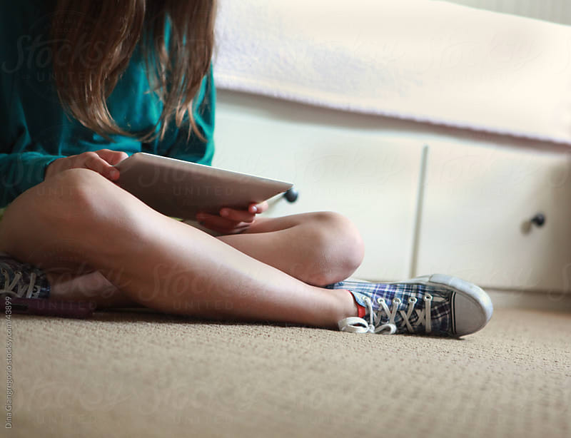 Teenager sitting on bedroom floor showing lower torso, legs and arms holding electronic tablet by Dina Giangregorio for Stocksy United