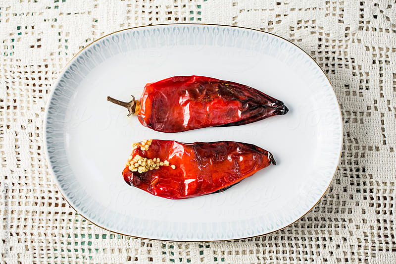 Two roasted red peppers on vintage plate by Lior + Lone for Stocksy United