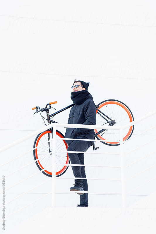 Trendy young male with his bike standing on stairs. by Audrey Shtecinjo for Stocksy United
