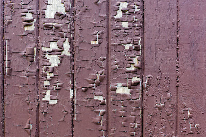 Cracked paint on the side of a brown, wooden barn. by Holly Clark for Stocksy United