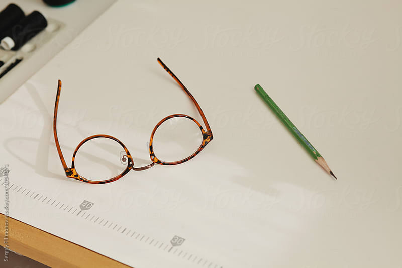 Vintage glasses and pencil lie on the sewing machine by Sergey Filimonov for Stocksy United