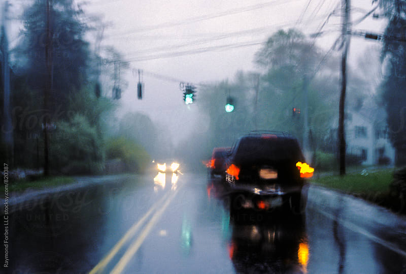 Approaching Stop Light in Rain Somewhere in New York by Raymond Forbes LLC for Stocksy United