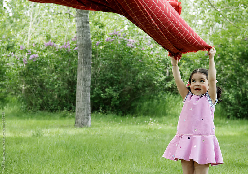 Young girl playing with a picnic blanket by W2 Photography for Stocksy United